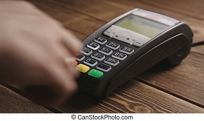 Hand swiping credit card on POS terminal - Mans hand pushing...