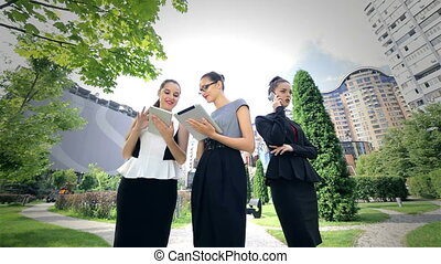 Three successful business woman working on tablets and...