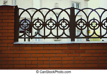 Black wrought iron and brick fence with home facade in...