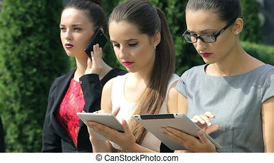 Three successful business woman sit together, take calls, and view the results