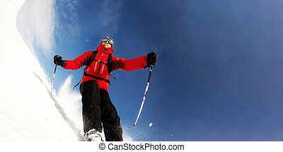 Skier in mountains performs a high speed turn on a ski piste