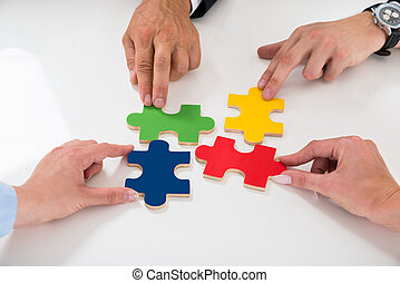 People Assembling Puzzle Pieces - Close-up Of People...