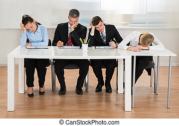 Businesspeople Getting Bored While Working In Office - Team...