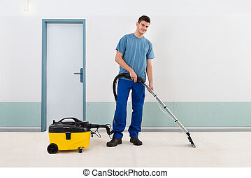 Male Cleaner Vacuuming Floor - Young Male Cleaner In Uniform...