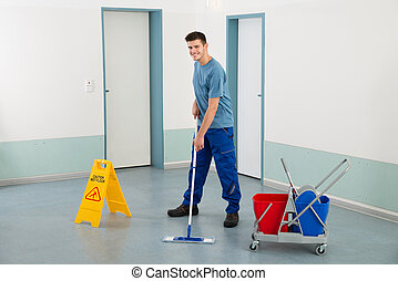 Male Worker With Cleaning Equipments Mopping Floor - Young...