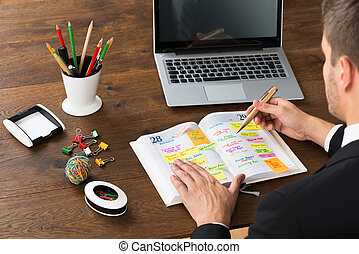 Businessman Writing Office Schedule At Desk - Close-up Of...