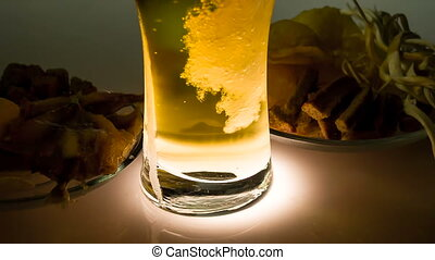 Cold Beer and Salty Snacks - In a glass of beer is poured...