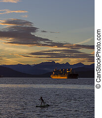 Paddle Boarder and Tanker - A paddle boarder at dusk at...