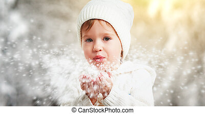 happy child girl blowing snowflakes in winter outdoors