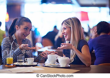 girls have cup of coffee in restaurant - happy girl friends...