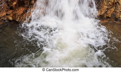 closeup stormy foamy stream falls into lake in park -...