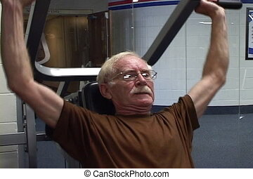 Senior Bodybuilder - Senior works his arms by working out on...