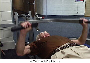 Senior Getting Fit - Senior man lays on a bench lifting a...