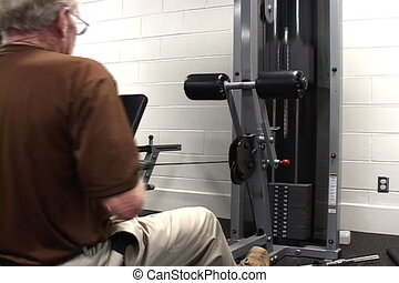 Senior Health - Senior adult man uses a weight lifting...