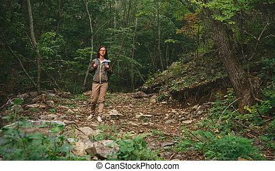 Hiker woman walking in summer forest