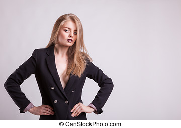 Woman with no bra in business suit on grey background Studio...