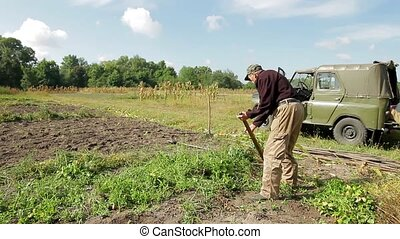 Farmer mows the grass Old man working in the field Work on...