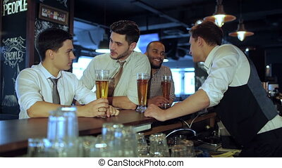 Activities of real men in a bar with beer - Four friends...