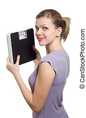 smiling young woman holding a weight scale over white...