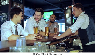 Relax after work - Four friends businessmen drink beer and...