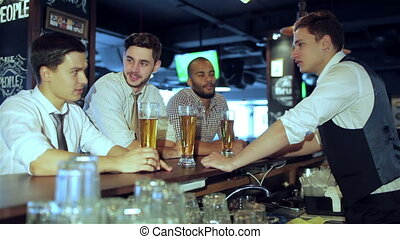 Three friends sitting at the bar and keep the beer
