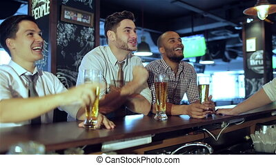 Men fans watching football on TV and drink beer