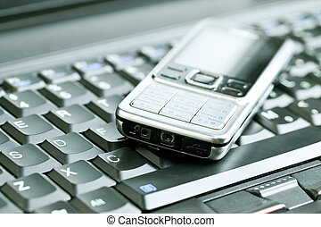 Business concept - mobile phone over laptop keyboard -...