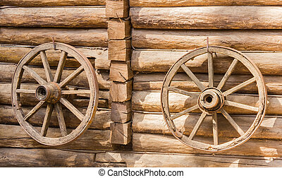 Two old cartwheel on a wooden wall - Two old wooden spoked...