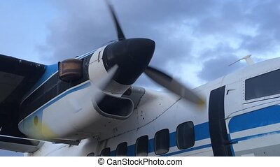 Rotating propeller plane on a background cloudy sky.