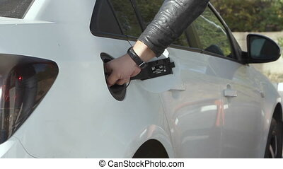 man pumping gasoline fuel in car at gas station. - Closeup...