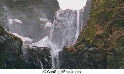 Wind blowing over waterfall in storm