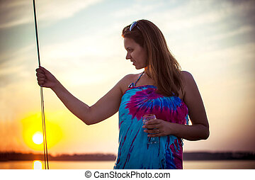 Gorgeous woman posing on yacht in beautiful mild sunset...