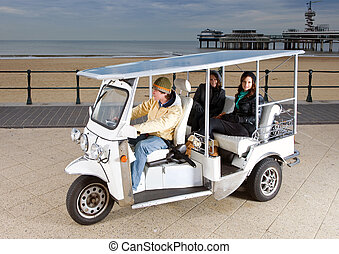 Solar powered cart at the beach, picking up two young women