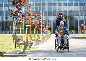 Social worker and disabled man on a walk