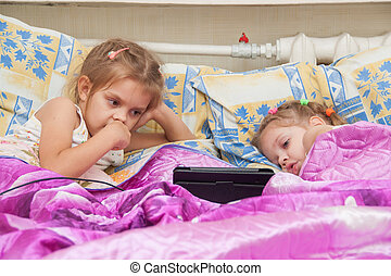 Two girls lying in bed looking at a tablet computer - Two...