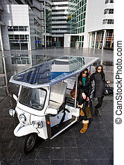 Solar powered tuc tuc - Two young women posing next to a...