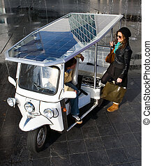 Solar powered tuc tuc - Young woman catching a ride in a...