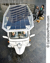 Solar powered tuc tuc - Two women looking at a solar powered...