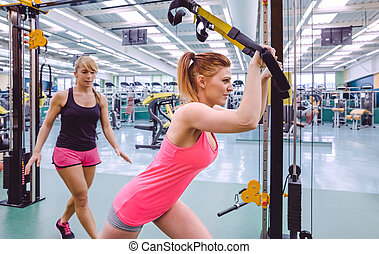 Personal trainer helping to woman in suspension training