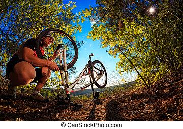 Man cyclist repairing a bike against blue sky - Man cyclist...