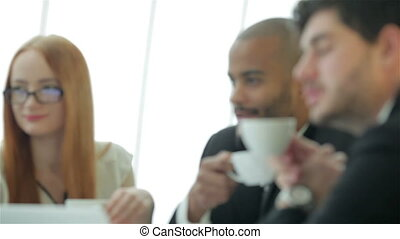 Four smiling successful businessmen drink coffee - Smiling...