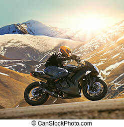 young man riding motorcycle on asphalt country road with sun...