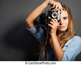 Young photographer in jeans jacket with old camera