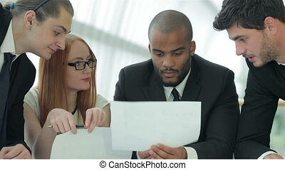 Businessmen sitting at table in office while discussing...