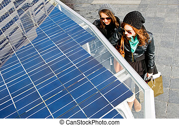 Solar powered tuc tuc - Two young women standing next to a...