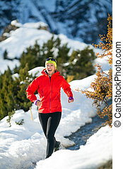 Cross country running in winter mountains - Woman running on...