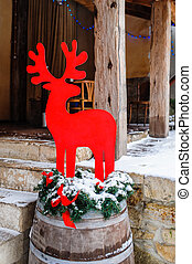 red decorative deer in front of the house