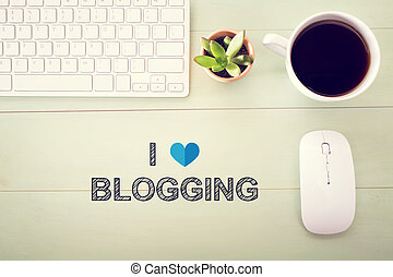 I Love Blogging concept with workstation on a light green...