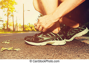 Male jogger tying his running shoes in preparation for a jog