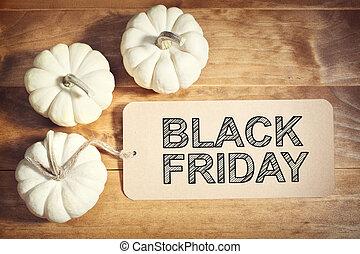 Black Friday message with small white pumpkins on wooden...